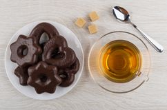Heap of figured gingerbreads in chocolate in plate, tea, sugar. Heap of figured gingerbreads in chocolate in plate, cup of tea, sugar and spoon on wooden table Stock Photos