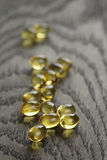 Heap of fish oil omega capsules on wooden table Stock Photo