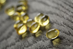 Heap of fish oil omega capsules on wooden table Royalty Free Stock Photo