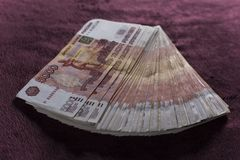Heap of five thousand russian rubles banknotes, stack on red velvet stock image