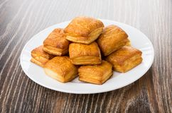 Heap of flaky biscuits in white plate on dark table Stock Images