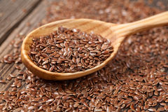 Heap of flax seeds in vintage wooden spoon Stock Photo