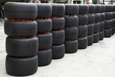 Heap of Formula 1 vehicle tyres in front of Pit stop garage Stock Image