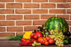 Heap of fresh fruits and vegetables. On brick wall background Royalty Free Stock Image