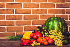 Heap of fresh fruits and vegetables. On brick wall background. Warm toned. Horizontal Royalty Free Stock Image