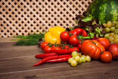 Heap of fresh fruits and vegetables. On a wooden lattice background Royalty Free Stock Photos