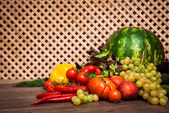 Heap of fresh fruits and vegetables. On a wooden lattice background.Horizontal Stock Photography