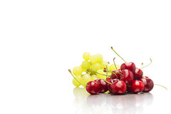 Heap of fresh organic cherries with green grapes Royalty Free Stock Photos