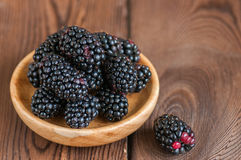 Heap of fresh raw blackberries in a plate on a wooden background. Copy space and close up Stock Photos