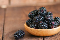 Heap of fresh raw blackberries in a plate on a wooden background. Copy space and close up Royalty Free Stock Photography