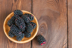 Heap of fresh raw blackberries in a plate on a wooden background. Copy space and close up. Top view Royalty Free Stock Image
