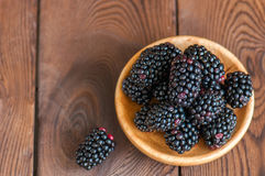 Heap of fresh raw blackberries in a plate on a wooden background. Copy space and close up. Top view Stock Photo