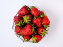 Heap of fresh strawberries in glass bowl on rustic white wooden background, isoated stock photography