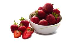 Heap of fresh strawberry put in white ceramic bowl, and some strawberry spread on white table. Heap of fresh strawberry put in white ceramic bowl, and some royalty free stock photography