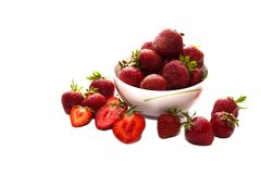 Heap of fresh strawberry put in white ceramic bowl, and some strawberry spread on white table. Heap of fresh strawberry put in white ceramic bowl, and some stock image
