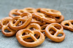 Heap of fresh Wheat salt pretzels on hessian linen. A group of fresh Wheat salt pretzels on hessian linen fabric cloth Royalty Free Stock Photography