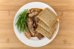Heap of fried bacon and dill in glass plate Royalty Free Stock Images