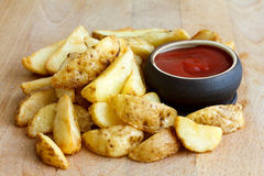 Heap of fried potato wedges on wood board with ketchup dip in bo Royalty Free Stock Photography