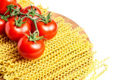 Heap fusilli bucati lunghi italian pasta and Fresh Red ripe tomatoes on a green branch laying on wooden beech board. Isolated on. White background royalty free stock photography