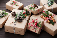 Heap of gift or present box wrapped in kraft paper with christmas decoration on rustic wooden background. Stock Images
