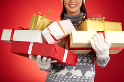 Heap of gifts. Smiling girl in gloves and pullover holding xmas wrapped gifts stock images