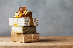 Heap of golden gift or present boxes on wooden table. Composition for birthday or christmas. royalty free stock image