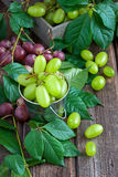 Heap of grapein bucket. Fresh  grape on  old wooden table Royalty Free Stock Photos