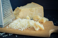 Heap of grated Parmesan. Cheese and metal grater on wooden board. Peace of Parmesan royalty free stock photography