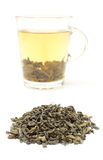 Heap of green tea and cup of beverage. White background Stock Photos