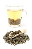 Heap of green tea and cup of beverage. White background Royalty Free Stock Photography