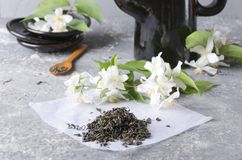 Heap of green tea on the white piece of paper, black teapot and plates, aromatic fresh jasmine flowers on the grey table stock image
