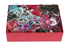 Heap of handsets. The lot of multi-colored broken earphones lies in a red cardboard box. Sound devices are prepared for utilization. Isolated Stock Photo