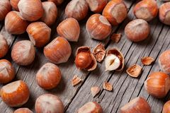 Heap Hazel and two nuts with  broken shell on an old wooden table Royalty Free Stock Photography
