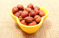 Heap of hazelnut in yellow cup on jute canvas Royalty Free Stock Images