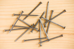 Heap of iron nails on wooden floor Royalty Free Stock Image