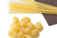 Heap of italian macaroni shells and spaghetti on brown napkin Royalty Free Stock Images