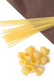 Heap of italian macaroni shells and spaghetti/pasta on napkin. Royalty Free Stock Photos