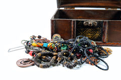 Heap of  jewelry. Heap of jewelry near wooden chest  on white background Stock Images