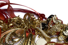 Heap of jewelry. Gold, jewels, a red tape, on a white background Royalty Free Stock Image