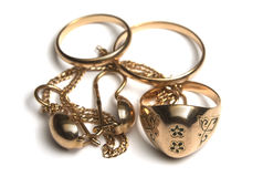 Heap of jewelry. Heap of gold jewelry isolated on white. Rings, ear ring and bracelet Royalty Free Stock Image