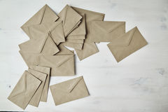 Heap of kraft paper brown envelopes on white wooden table.  Royalty Free Stock Photo
