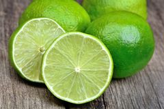 Heap of limes on vintage wood table. Close up royalty free stock photography
