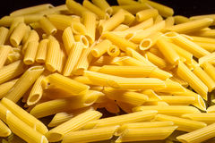 Heap of macaroni noodles reflecting on black background Royalty Free Stock Images