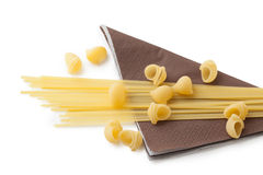Heap of macaroni shells and spaghetti on brown napkin Royalty Free Stock Images