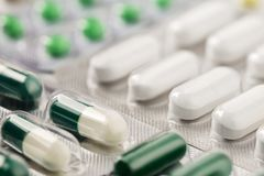 Heap of medical pills in white, green and other colors. Herbal medical pills. Pills in plastic package. Concept of healthcare and. Heap of medical pills in white royalty free stock image