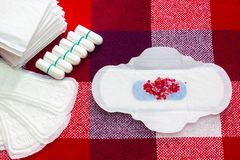 Heap of menstruation sanitary soft pads with red beads and cotton tampon for woman hygiene protection. Woman critical days, gyneco. Heap of menstruation sanitary royalty free stock photography