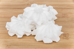 Heap of meringue on wooden table Stock Photo