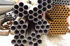 Heap of metal pipes in outdoor warehouse Stock Image
