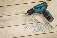 Heap of metal screws and electric drill royalty free stock photos