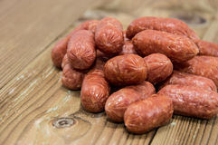 Heap of mini Salamis on wooden background Stock Image